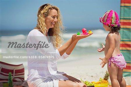 Femme donnant des jouets à sa fille sur la plage