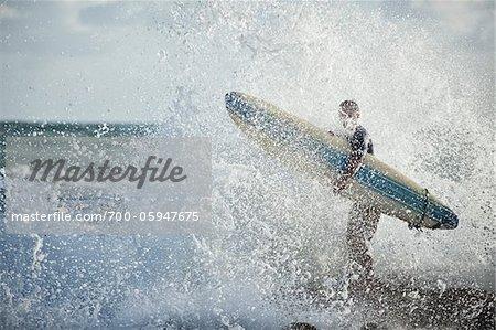 Surfer on Rocks Getting Splashed by Wave