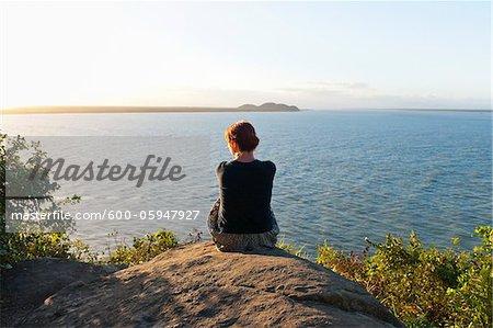 Backview de femme assise sur la colline, Ilha do Mel, Parana, Brésil