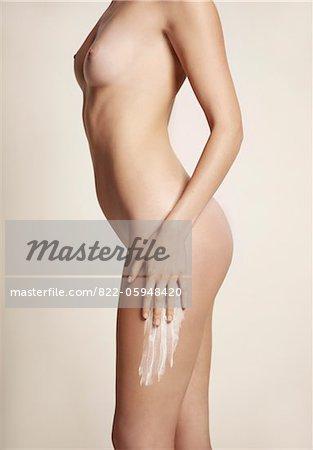 Vue latérale d'une femme nue, appliquer la lotion pour le corps sur la cuisse