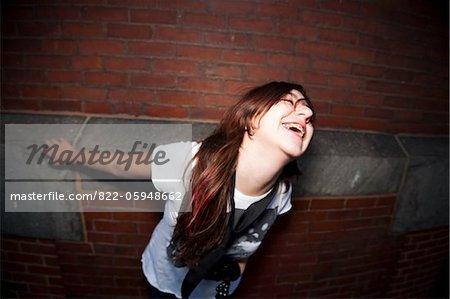 Teenage Girl devant rire de mur de brique