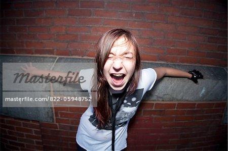 Teenage Girl steht vor Brick Wall schreien