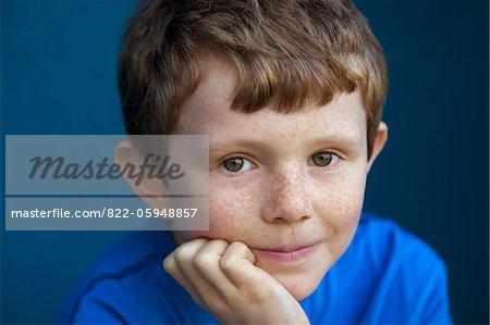 Portrait de garçon avec la main sur le menton