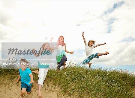 Children playing on grassy sand dune