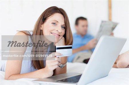Femme achats en ligne sur lit