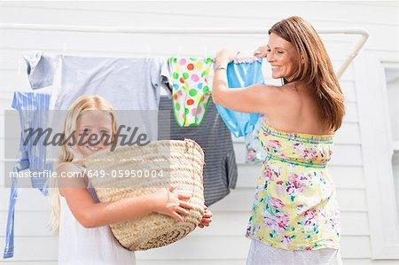 Mädchen helfen Mutter hängt Wäsche