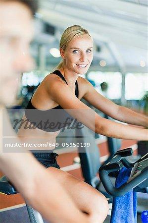Femme à l'aide de la machine d'exercice dans la salle de gym