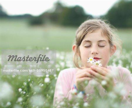 Fille odeur de fleurs dans la prairie