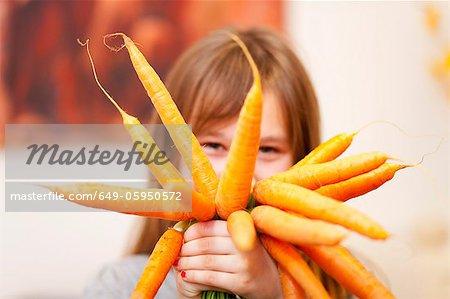 Jeune fille souriante tenant des tas de carottes