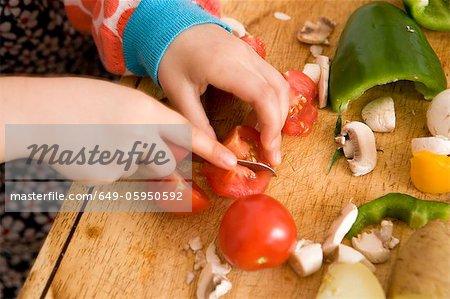 Gros plan de l'enfant pour trancher les légumes