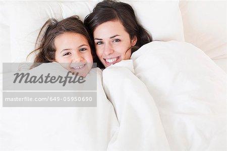 Mère et fille relaxante dans son lit
