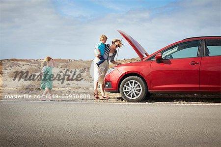Mother examining broken down car