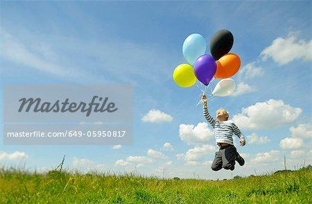 Garçon jouant avec des ballons dans la prairie