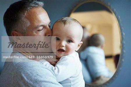Gros plan du père embrassant bébé