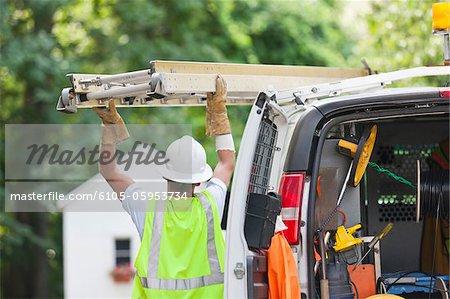 Travailleur Communications une échelle dans un camion de chargement