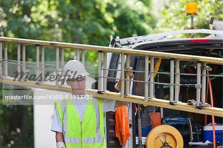Travailleur communications transportant une échelle du camion pour réaliser l'installation