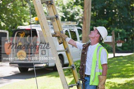 Travailleur communications prépare à gravir pour le câblage au pavillon