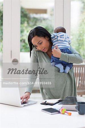 Jeune femme tenant le bébé et l'utilisation d'ordinateur portable