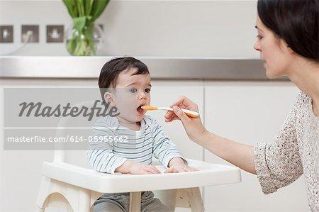 Mère fils alimentation de bébé dans la chaise haute