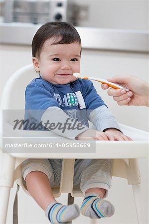 Adultes alimentation bébé dans la chaise haute