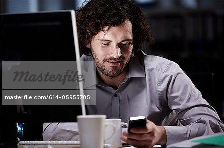Blick auf Handy im dunklen Büro Büroangestellter