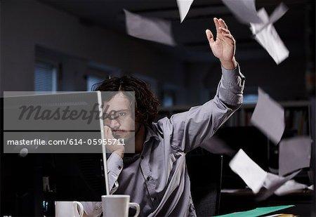Büroberuf arbeiten spät, Papier in die Luft werfen