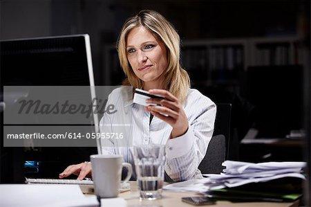 Geschäftsfrau im dunklen Büro, mit Kreditkarte online