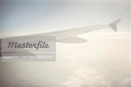 Wing of aeroplane flying in sky