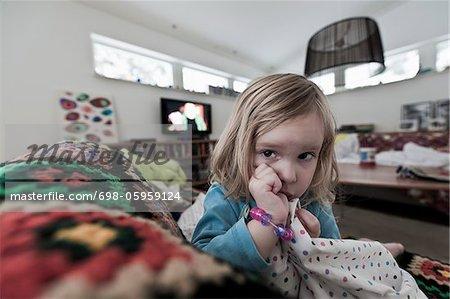 Jeune fille aux cheveux blonde sucer le pouce en s'appuyant sur le canapé