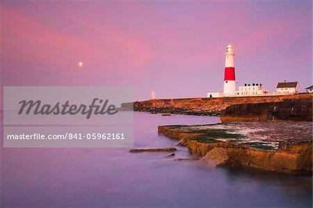 Une pleine lune dans le ciel de l'aube au phare de Portland Bill, Côte Jurassique, patrimoine mondial de l'UNESCO, Dorset, Angleterre, Royaume-Uni, Europe