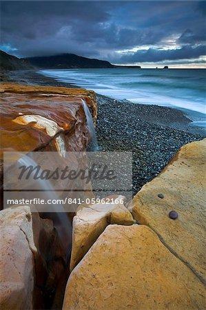 Chutes d'eau en cascade sur un grès rouge sur Seven Mile Beach, île du Sud, Nouvelle-Zélande, Pacifique