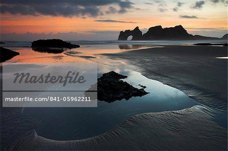 Lever du soleil sur la plage de Wharariki en haut de l'île du Sud, Nouvelle-Zélande, Pacifique
