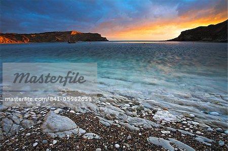 Coucher de soleil sur la baie circulaire à Lulworth Cove, Côte Jurassique, patrimoine mondial de l'UNESCO, Dorset, Angleterre, Royaume-Uni, Europe
