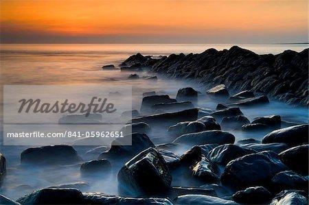 Misty water swirling around wet rocks at Kimmeridge Bay, Jurassic Coast, UNESCO World Heritage Site, Dorset, England, United Kingdom, Europe