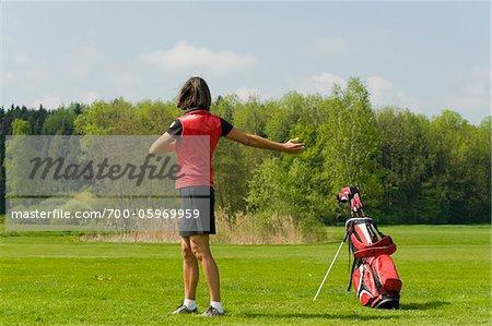 Frau, dehnen, bevor Sie spielen Golf