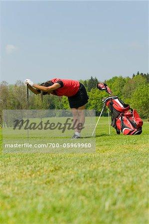 Frau Dehnung auf Golfplatz