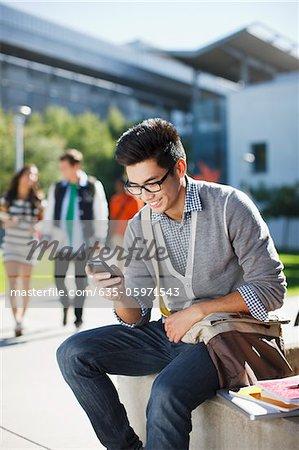 Étudiante souriante à l'aide de téléphone portable à l'extérieur