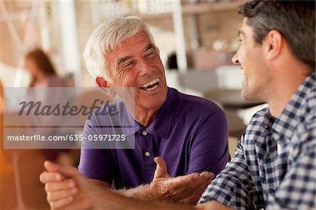 Männer lachen zusammen im cafe