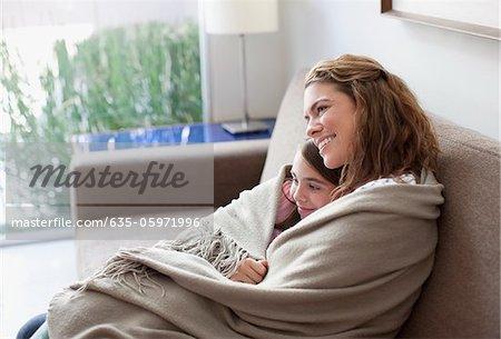 Mère et fille, enveloppé dans une couverture sur canapé