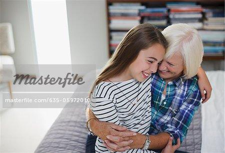 Ancienne femme étreignant petite-fille à l'intérieur