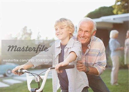 Vieil homme aidant bicycle ride petit-fils