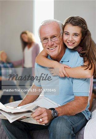 Mädchen knuddeln Großvater zu Hause