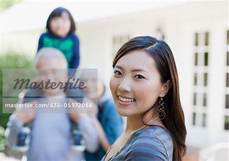 Femme souriant avec la famille à l'extérieur