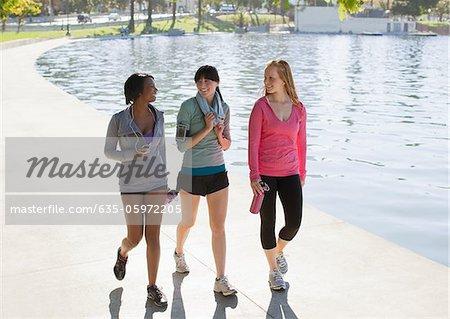 Women walking along lake in park