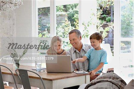 Familie mit Laptop zusammen am Esstisch
