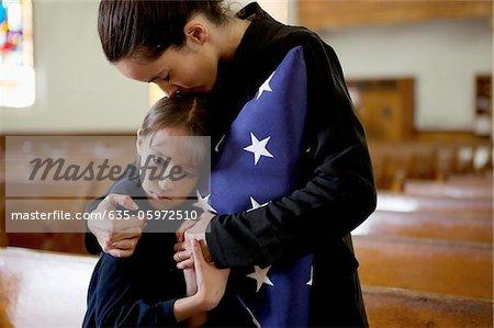 Mutter und Tochter bei militärischen Beerdigung knuddeln