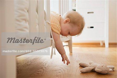 Bébé fille atteignant hors berceau pour obtenir le jouet en peluche