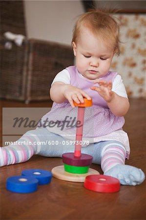 Baby-Mädchen sitzen auf Boden mit Spielzeug spielen