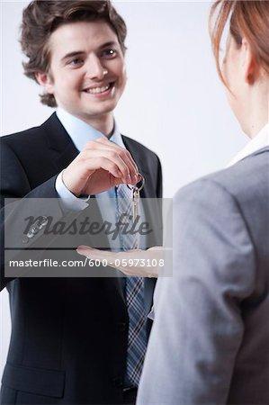 Junger Geschäftsmann, Geschäftsfrau Schlüsseln einzuräumen
