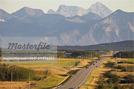 Ländliche Straße und Rocky Mountains, Pincher Creek, Alberta, Kanada